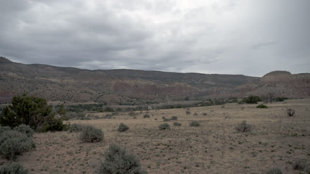 wide angle of desert landscape with overcast sky. shrubs and trees visible. rolling hills or mountains and buttes or mesas partially visible in bg. american southwest, could be arizona. - 2014 stock videos & royalty-free footage