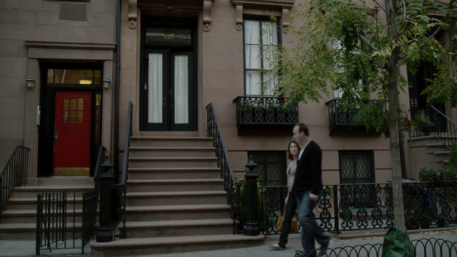 stockvideo's en b-roll-footage met pan down medium angle of entrance to brownstone apartment building or townhouse. could be west village. trees visible. pedestrians visible. - stadswoning
