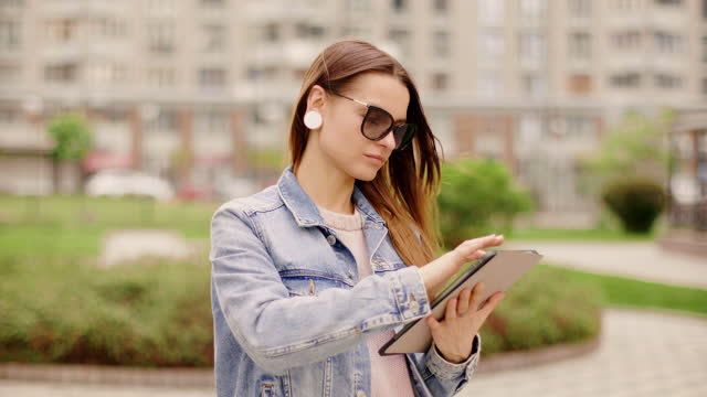 vidéos et rushes de привлекательная молодая деловая женщина использует планшет на фоне города - 25 29 years