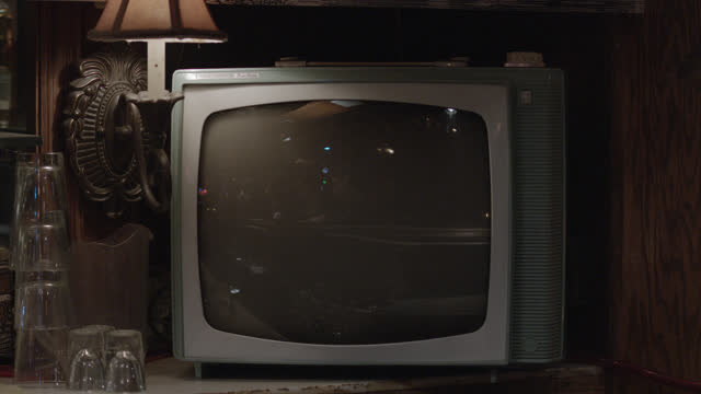 close angle of analog television on shelf. glasses and shot glasses visible . could be bar or tavern. - 1956 stock videos & royalty-free footage