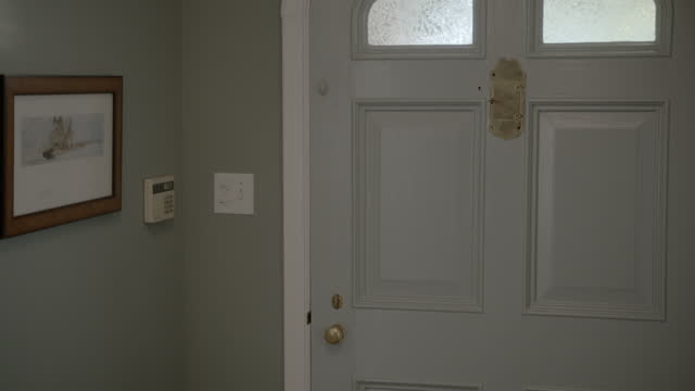 medium angle of front door of upper or middle class house. small frosted windows visible. art hangs on wall near alarm system keypad. gold peephole with cover visible. - 2013 stock videos & royalty-free footage