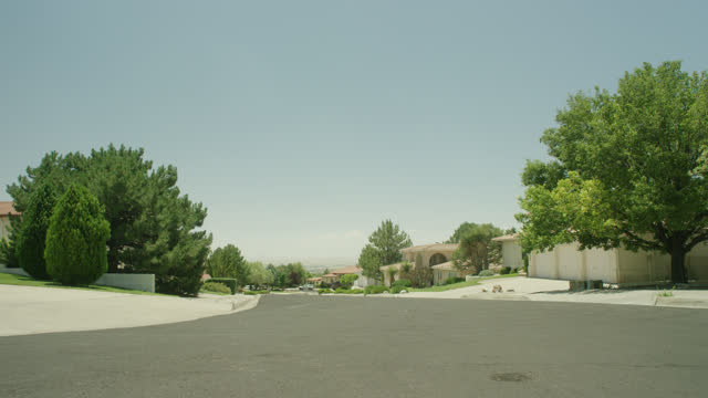 wide angle of road or street in upper middle class residential area or neighborhood. could be suburbs. trees and houses visible. - new mexico stock videos & royalty-free footage