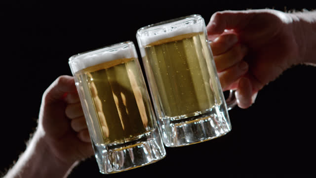 close angle of two beer glasses, mugs, or steins being touched or clinked together in slow motion. could be celebratory toast or celebration. could be bar. mens hands and arms visible. black bg. vfx library. - 2015 stock videos & royalty-free footage