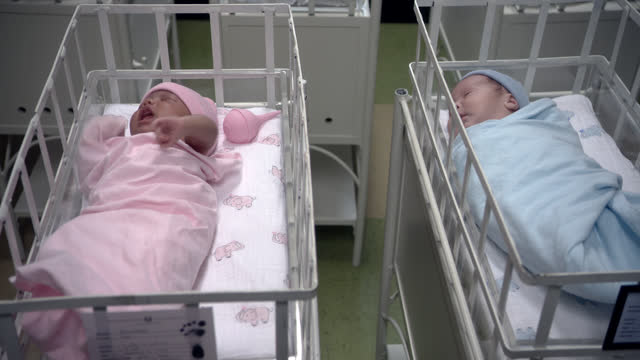 close angle of two babies wrapped in blue and pink blankets and wearing blue and pink hats in bassinets in hospital. could be nursery in maternity ward. nurse in uniform partially visible in bg. - 1956 stock videos & royalty-free footage