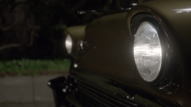 close angle of headlights flashing on classic car. sidewalk partially visible in bg. - headlight stock videos & royalty-free footage