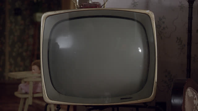 close angle of classic television set. tv turned off. could be living room. baby doll in high chair visible in bg. lights flash in room. could be camera flash. - 1956 stock videos & royalty-free footage