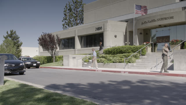 wide angle of entrance of santa clarita courthouse. american flag visible. police car and police officer or security visible. people enter and exit building. - santa clarita bildbanksvideor och videomaterial från bakom kulisserna