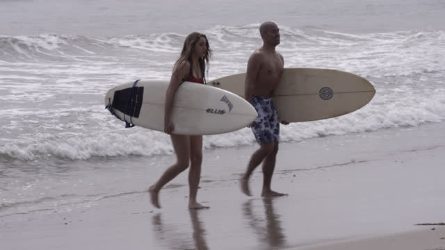 medium angle of man and woman carrying surfboards exiting ocean. additional woman in bikini walks by from fg to bg. - malibu stock videos & royalty-free footage