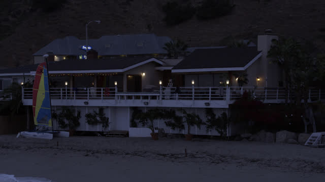 pan left to right medium angle from ocean to beach house with patio or balcony. volleyball net and sailboat visible in front of house. beach and ocean visible.  surfers visible walking with surfboard from left to right. - malibu stock videos & royalty-free footage