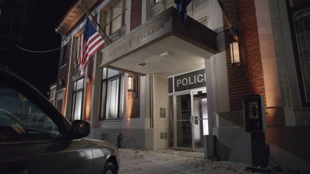 close angle of entrance of police station. cars parked in parking lot at entrance of building partially visible. brick multi-story building. police detectives visible entering building. pay phone visible. - police station stock videos & royalty-free footage
