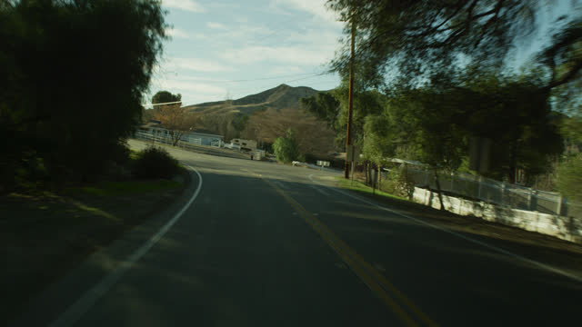 vídeos de stock e filmes b-roll de process plate straight back of car driving on rural area or country road. tree, wood fences, and telephone poles visible. house or small ranch visible. could be farm. could be mountain road. - santa clarita