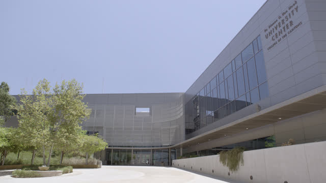 medium angle of courtyard and multi-story modern silver building. could be office building, hospital, medical center, or university. building is dr. dianne g. van hook university center college of the canyons. some people visible walking in bg. - courtyard stock videos & royalty-free footage