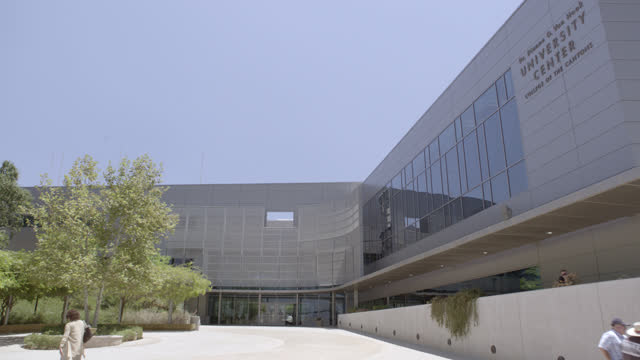 medium angle of courtyard and multi-story modern silver building. could be office building, hospital, medical center, or university. building is dr. dianne g. van hook university center college of the canyons. some people visible walking in courtyard. - courtyard stock videos & royalty-free footage