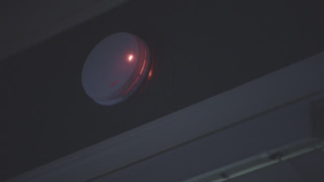 vidéos et rushes de up angle close angle of smoke detector or alarm in house or apartment. door frame partially visible. red light blinks on alarm. - sécurité