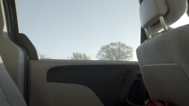 close angle from inside backseat of car. could be child pov. camera faces left back window. blue sky and clouds, trucks, and trees partially visible. american southwest, could be arizona. - passenger seat stock videos & royalty-free footage