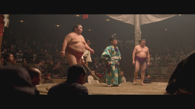 medium angle of a sumo wrestling match in an arena or auditorium. raised ring is covered in clay and sand. crowd applauds as two wrestlers face off and perform pre match rituals of bowing, squatting, and tossing sand on ring. several men holding banners w - 1920 1929 stock videos & royalty-free footage
