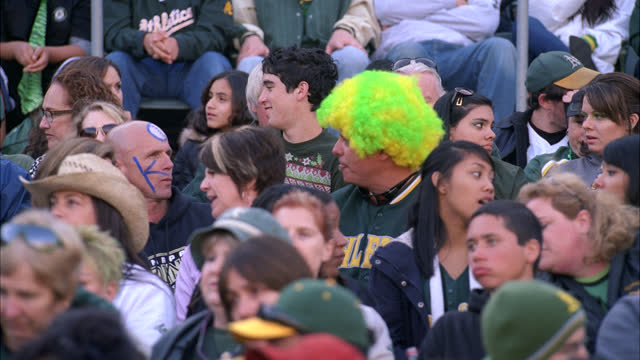 stockvideo's en b-roll-footage met medium angle of oakland athletics baseball fans sitting in stadium stands. people wearing oakland 'a's' baseball caps, sweatshirts, jackets, ten-gallon cowboy hats. camera pans crowd as they begin to clap, applaud, cheer and stand up. some fans holding or - hoofddeksel