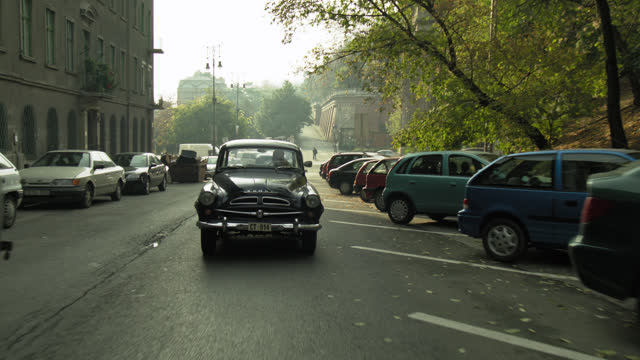 vidéos et rushes de process plate straight back of classic cars driving across chain bridge over the river danube in budapest with gresham palace in bg. pass hungarian flags hanging on side of bridge, lion capstones, multi-story buildings, could be apartment buildings or, an - chain bridge suspension bridge