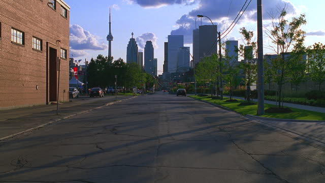 dusk/early evening toronto, ontario, canada urban street; light activity; city skyline visible at end of street - pavement stock videos & royalty-free footage