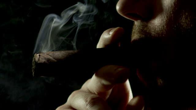zigarre rauchen auf schwarz-zeitlupe - 1080hd - zigarre stock-videos und b-roll-filmmaterial