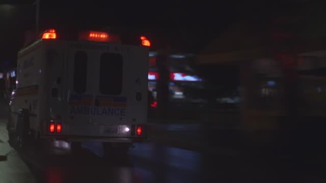 n/x camera follows cube ambulance thru n-d city streets, lights on - blaulicht stock-videos und b-roll-filmmaterial