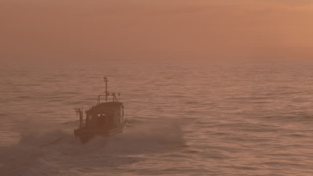 aerial sunset fishing boat on ocean away from camera toward horizon - fishing industry stock videos & royalty-free footage
