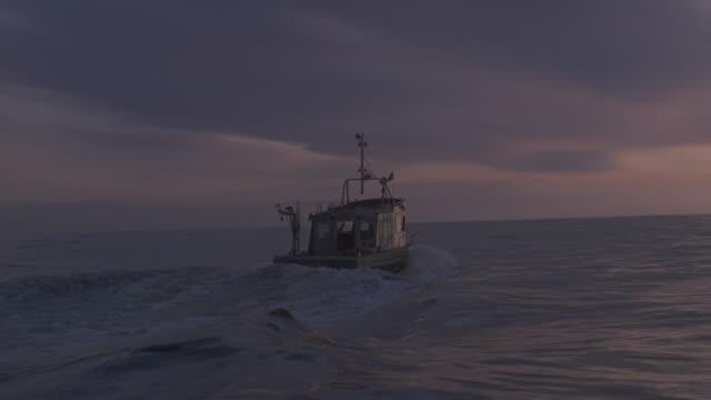 sunset fishing boat on ocean away from camera toward horizon - fishing industry stock videos & royalty-free footage