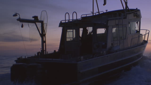 vidéos et rushes de sunset fishing boat on ocean away from camera toward horizon - chalutier