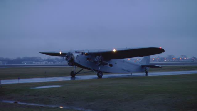 dusk 1930's-era ford tri-motor propeller plane taxi's, n-d airport (chicago) - propeller video stock e b–roll