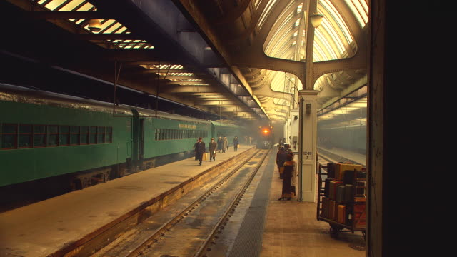 period 1930's passenger train pulls into station, stops; people in period costume visible on platform - dampf stock-videos und b-roll-filmmaterial