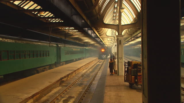 period 1930's passenger train pulls into station, stops; people in period costume visible on platform - bahnreisender stock-videos und b-roll-filmmaterial