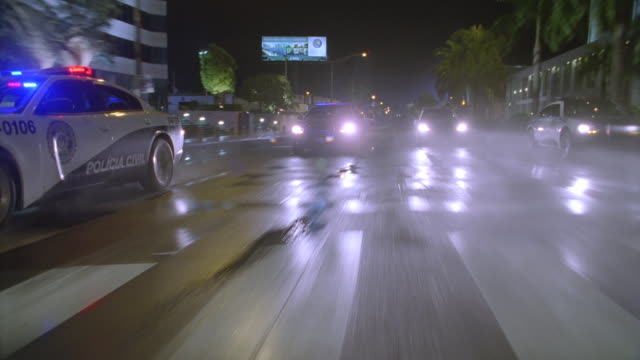 n/x camera leads 4 rio police cars fast thru city streets, lights on - sequential series stock videos & royalty-free footage