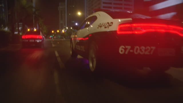 vidéos et rushes de n/x camera trails 4 rio police cars fast thru city streets, lights on - suit