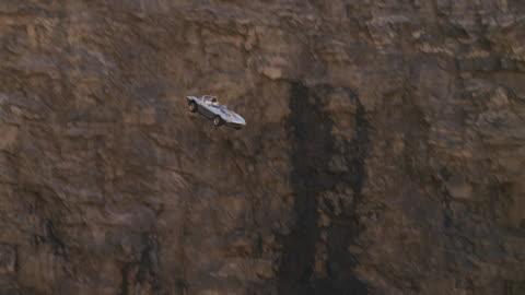 stockvideo's en b-roll-footage met silver  convertible sports car flies off of cliff, plunges into water below - klif