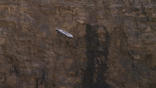 silver  convertible sports car flies off of cliff, plunges into water below - klippe stock-videos und b-roll-filmmaterial