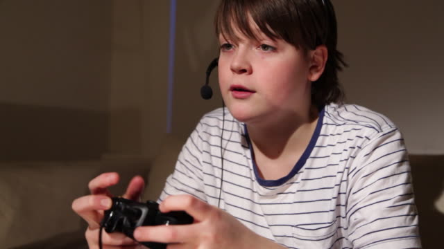 BOY AGED 12 PLAYING COMPUTER GAME
