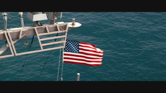 aerial u.s. flag flying atop guided missile destroyer uss john paul jones ddg-53; pull back to wide shot ship away from camera - us military stock videos & royalty-free footage