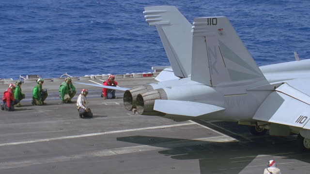 navy jet prepares for t/o on deck of aircraft carrier - motore d'aeroplano video stock e b–roll