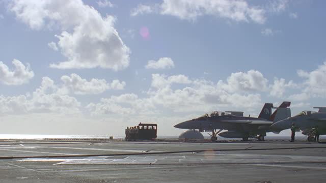 jet lands on aircraft carrier - reißschwenk stock-videos und b-roll-filmmaterial