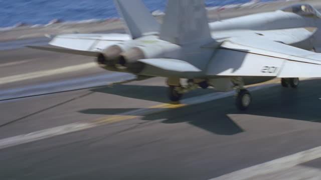 navy jet lands on aircraft carrier - reißschwenk stock-videos und b-roll-filmmaterial