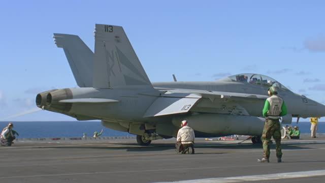 navy jet t/o from aircraft carrier - reißschwenk stock-videos und b-roll-filmmaterial