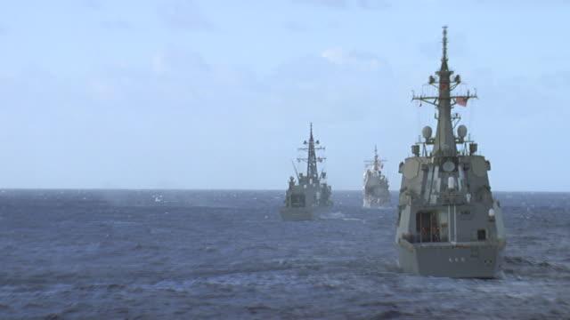 convoy of 3 navy ships at sea; 3rd ship fires large caliber gun - convoy stock videos & royalty-free footage