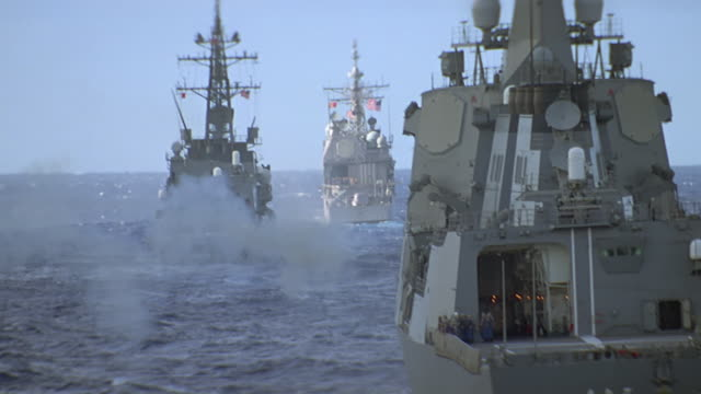 convoy of 3 navy ships at sea; 3rd ship fires large caliber gun - marine stock-videos und b-roll-filmmaterial