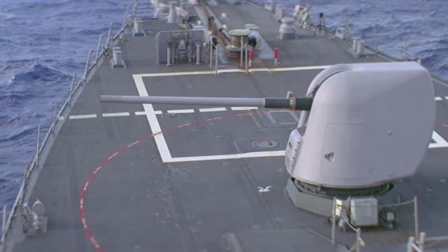 large caliber gun fires from deck of navy ship - reißschwenk stock-videos und b-roll-filmmaterial