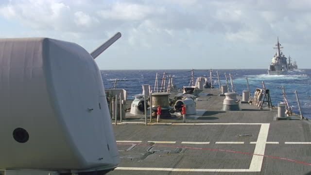 vidéos et rushes de large caliber gun fires from deck of navy ship - marine américaine