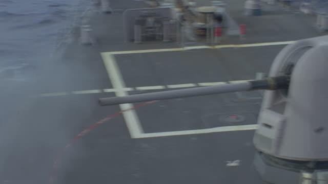 large caliber gun fires from deck of navy ship - スウィッシュパン点の映像素材/bロール