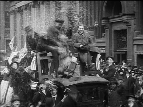 B/W 1918 men sitting on car in crowded street cheering during Armistice Day parade / WW I