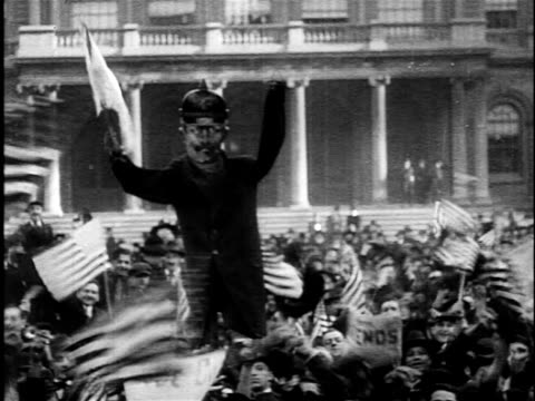 b/w 1918 crowd waving us flags holding cariacature of german / armistice day ww i - armistizio video stock e b–roll