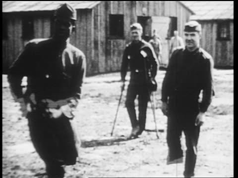 B/W 1910s wounded World War I veterans in uniform playing baseball / onelegged man pitching / news