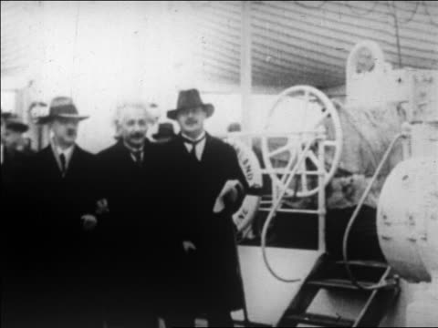 Albert Einstein walking on ship with two men / they stop pose / newsreel